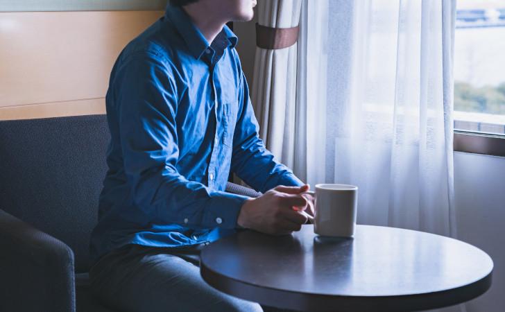 コーヒーを飲みながら外を眺める男性